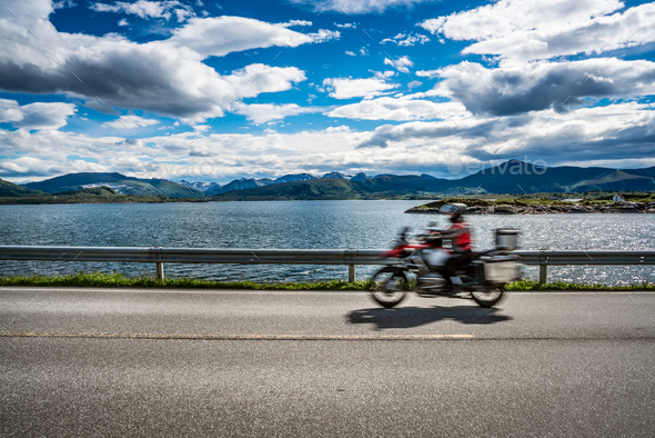 Biker rides a road with Atlantic Ocean Road in Norway. - Stock Photo - Images