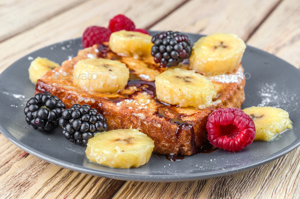 French toast with fried banana and berries in natural wood - Stock Photo - Images