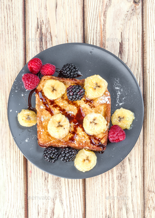 vertical shot of a French toast with fried banana and berries in natural wood - Stock Photo - Images