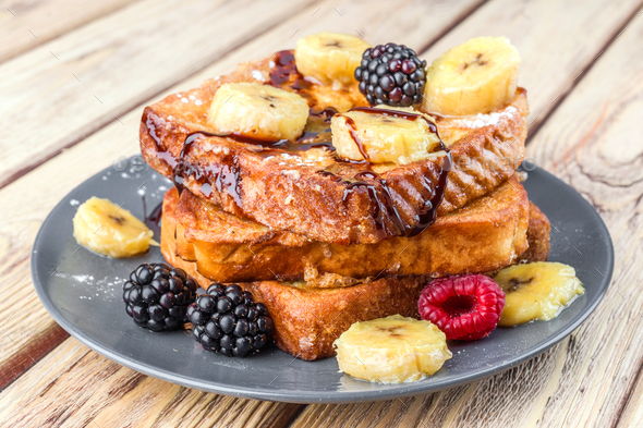 Tower of french toast with fried plantain and berries in natural wood - Stock Photo - Images