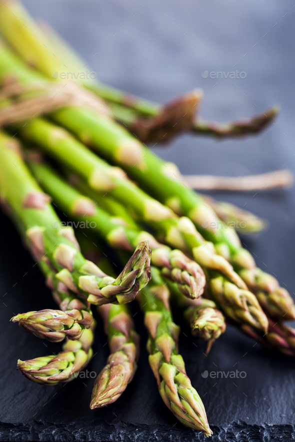 Raw fresh asparagus on dark background, close-up - Stock Photo - Images
