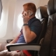 A Young Man in an Airplane Before a Flight Communicates on a Mobile Phone - VideoHive Item for Sale