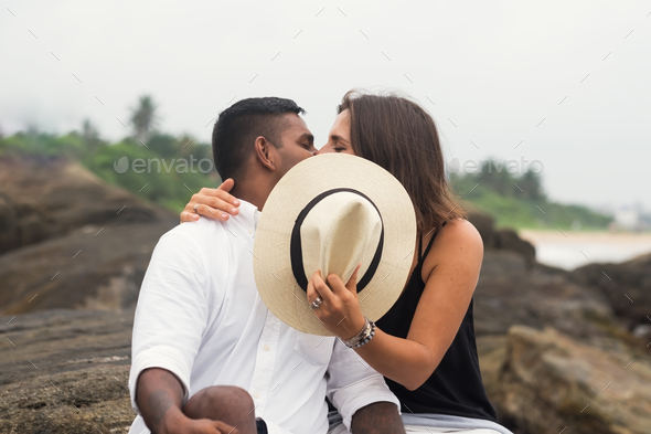 Young mixed race couple kissing sitting on stone. They close faces with hat. - Stock Photo - Images