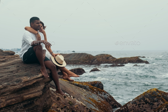 Young couple on the stone neat ocean - Stock Photo - Images