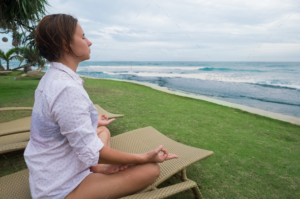 caucasian woman meditates sitting in chair on the beach - Stock Photo - Images