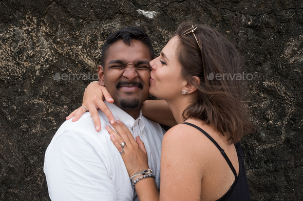 Outdoor portrait of romantic kissing young couple in sandy beach. - Stock Photo - Images