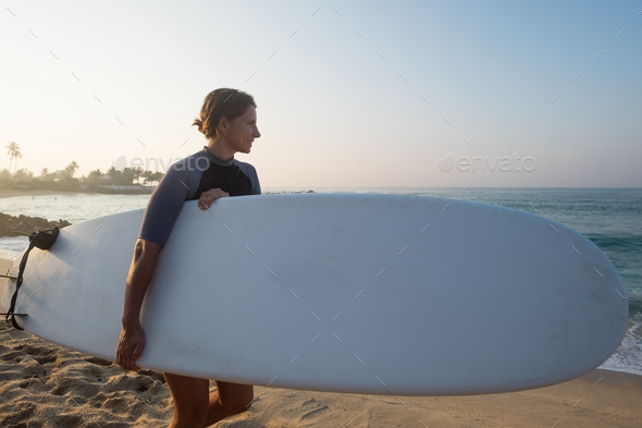 caucasian woman with surfboard standing near water and looking at waves. - Stock Photo - Images