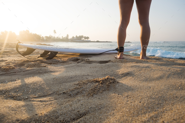 Young caucasian woman surfer with surfboard in the morning - Stock Photo - Images