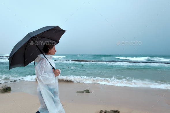 Young woman walking with an umbrella in front of ocean in rainy weather - Stock Photo - Images