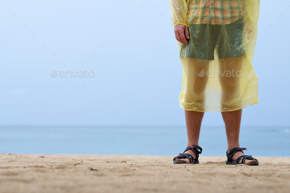 man on ocean or sea coast in rain coat - Stock Photo - Images