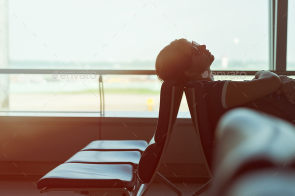 Tired caucasian woman sleeping in airport lounge waiting for flight - Stock Photo - Images