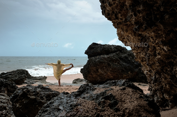 Woman in rain coat doing balance yoga asana on ocean beach during storm. - Stock Photo - Images
