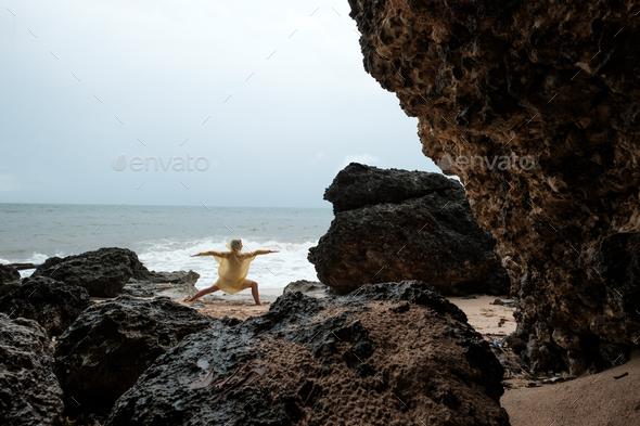 Woman in rain coat doing balance yoga asana on ocean beach during storm. - Stock Photo - Images
