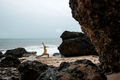 Woman in rain coat doing balance yoga asana on ocean beach during storm. - PhotoDune Item for Sale