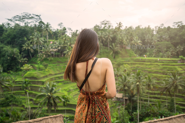 Young woman looking at beautiful tegallalang rice terrace - Stock Photo - Images