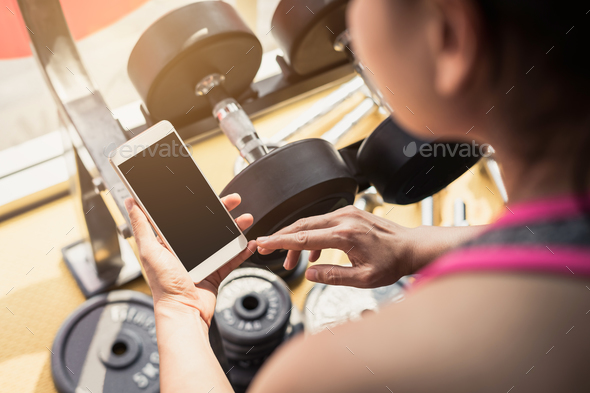 Young asian woman using smartphone in gym - Stock Photo - Images