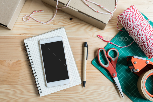 Empty screen smart phone with cardboard boxes - Stock Photo - Images