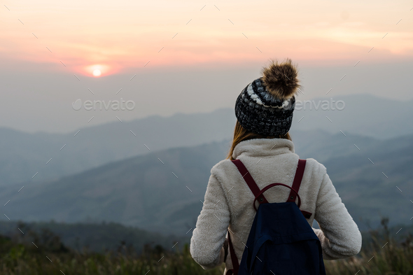 Young woman traveler looking at sunrise - Stock Photo - Images