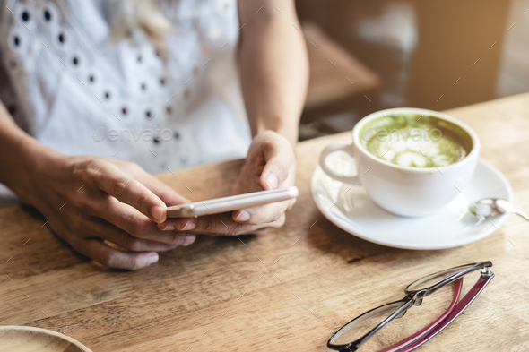 Young woman using smart phone and drinking coffee in cafe - Stock Photo - Images