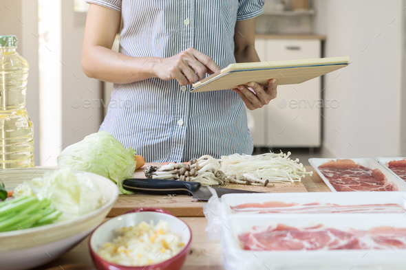 Young woman using her touchpad in the kitchen - Stock Photo - Images