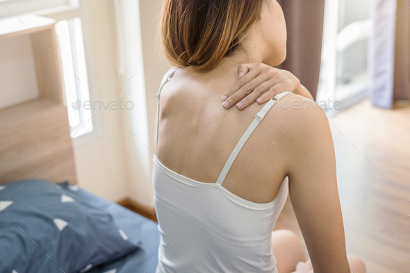 Woman suffering from neck pain on the bed - Stock Photo - Images