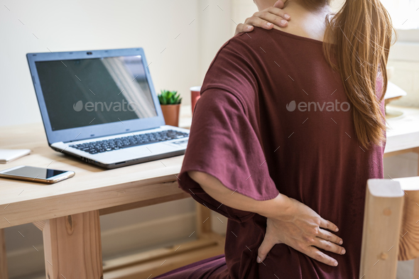 Young woman working at home and having back pain - Stock Photo - Images