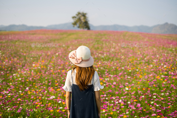 Young woman traveler standing and looking beautiful blooming flowers field - Stock Photo - Images