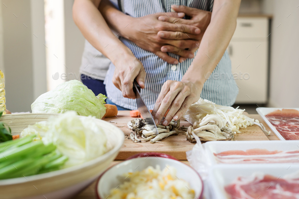 Young asian couple cutting vegetable in the kitchen - Stock Photo - Images