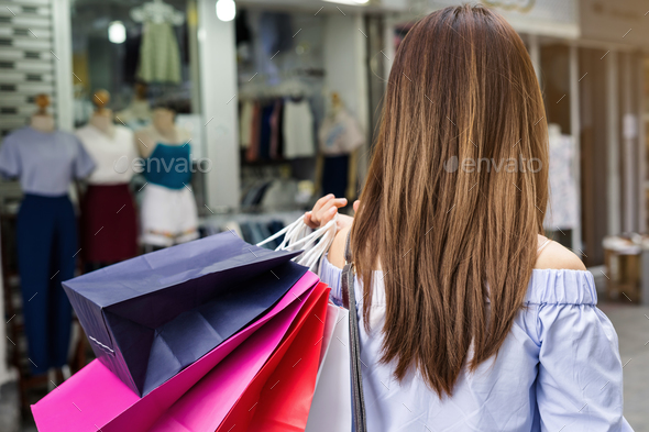 Young woman with shopping bags in the shop - Stock Photo - Images