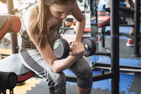 Young asian women lifting dumbbell in sport gym - Stock Photo - Images