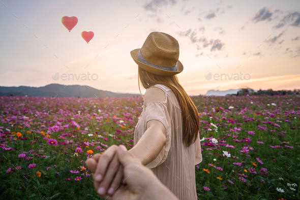 Young woman traveler holding man's hand and leading him - Stock Photo - Images