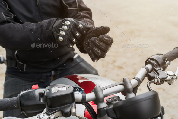 Biker with jacket wearing protect glove and riding motorbike - Stock Photo - Images