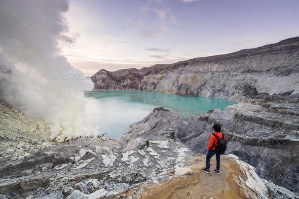 Young travler looking crater blue lake at Kawah Ijen, Indonesia - Stock Photo - Images