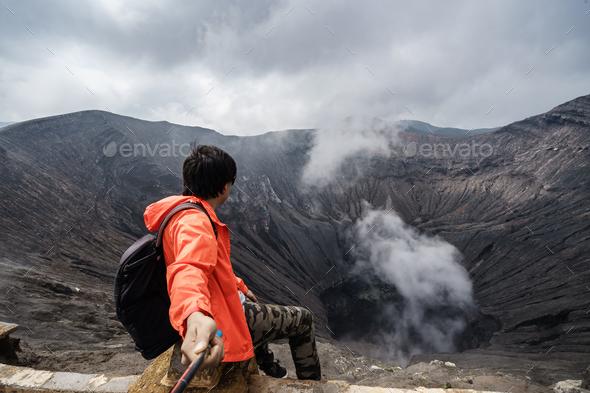 Traveler at crater volcano at Bromo (Gunung Bromo), Indonesia - Stock Photo - Images