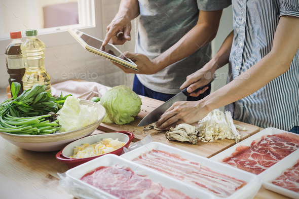 Young asian couple cutting vegetable and using touchpad - Stock Photo - Images