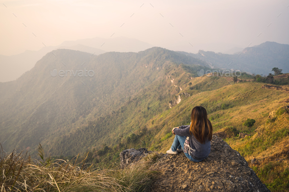 Young woman traveler sitting and looking at beautiful landscape - Stock Photo - Images