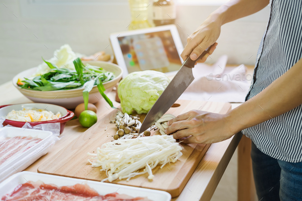 Young asian woman cutting vegetable in the kitchen - Stock Photo - Images