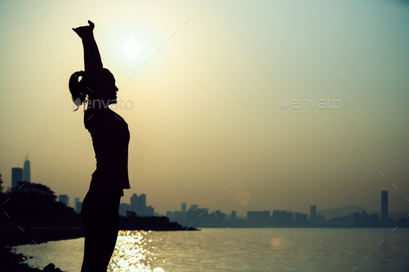 Silhouette of woman stretching arms during sunrise - Stock Photo - Images