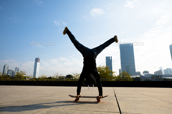 Skateboarder doing a handstand on skateboard in modern city - Stock Photo - Images