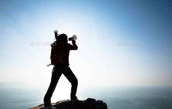 Woman shouting with loudspeaker on sunrise seaside - Stock Photo - Images