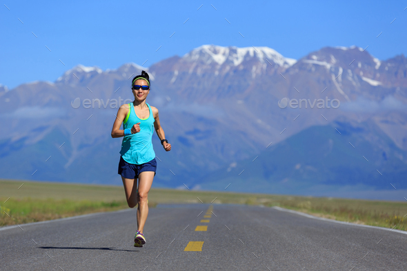 Determined woman runner running on mountain trail - Stock Photo - Images