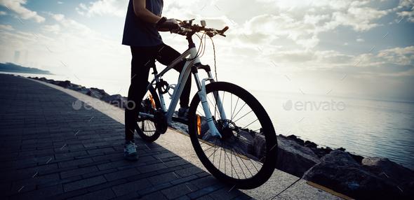 Woman cyclist using mobile phone while riding mountain bike on sunrise coast - Stock Photo - Images