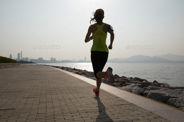 Morning exercise jogging on sunrise coast - Stock Photo - Images