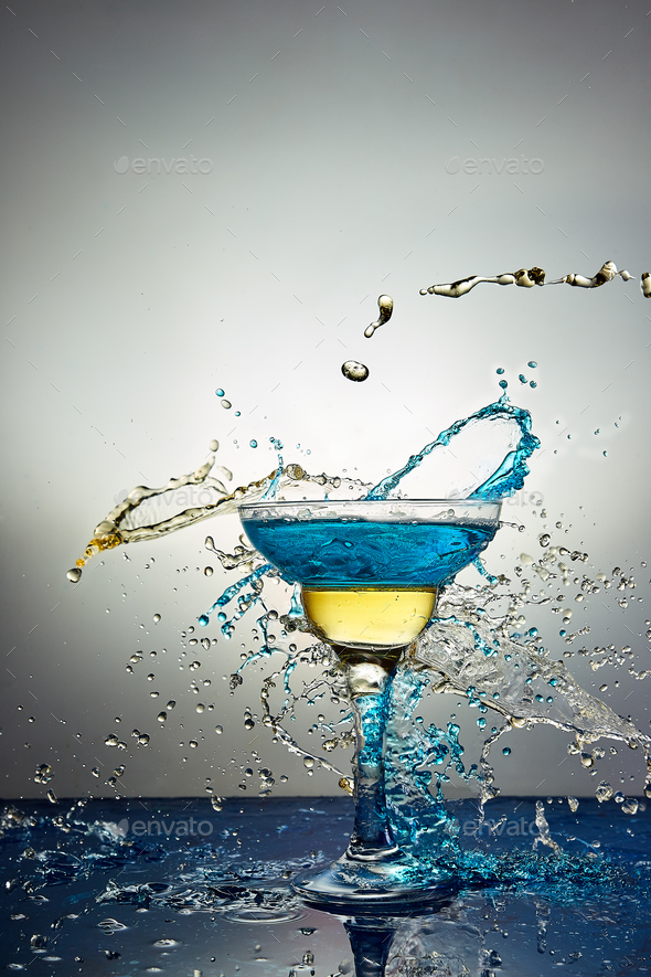 Glass with blue and yellow  champagne or cocktail. Levitation - Stock Photo - Images