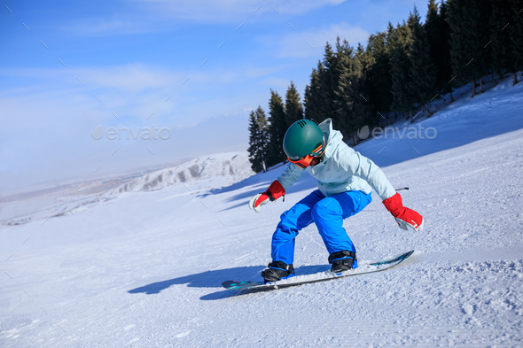 Snowboarding descent on mountain slope - Stock Photo - Images