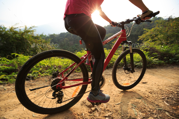 Riding mountain bike on sunrise trail - Stock Photo - Images