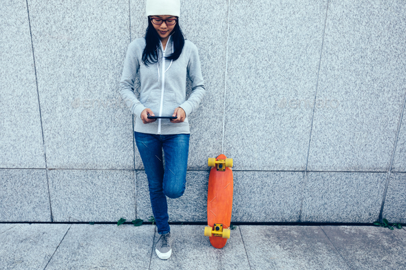 Woman skateboarder use mobile phone against wall in city - Stock Photo - Images