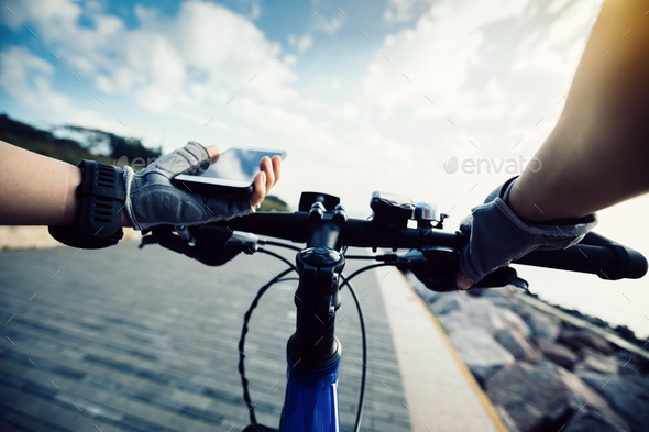 Cyclist hands use mobile phone - Stock Photo - Images