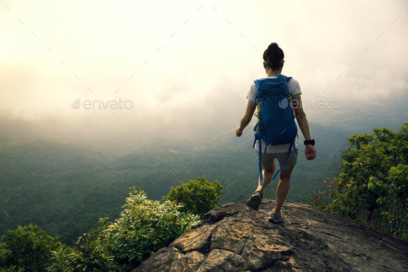 Hiking on mountain top cliff edge - Stock Photo - Images