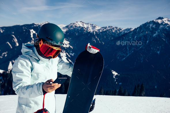 Snowboarder use mobile phone on alpine mountain top - Stock Photo - Images